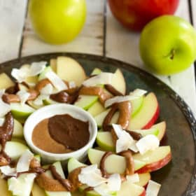 a plate of healthy apple nachos with apples on a white board