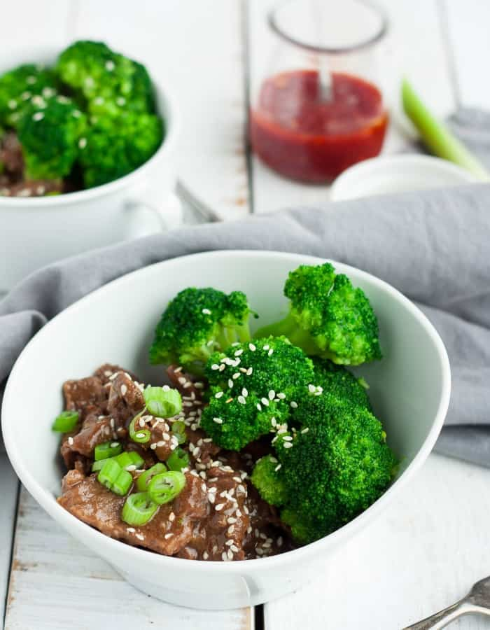 two bowls of instant pot paleo beef and broccoli with hot sauce