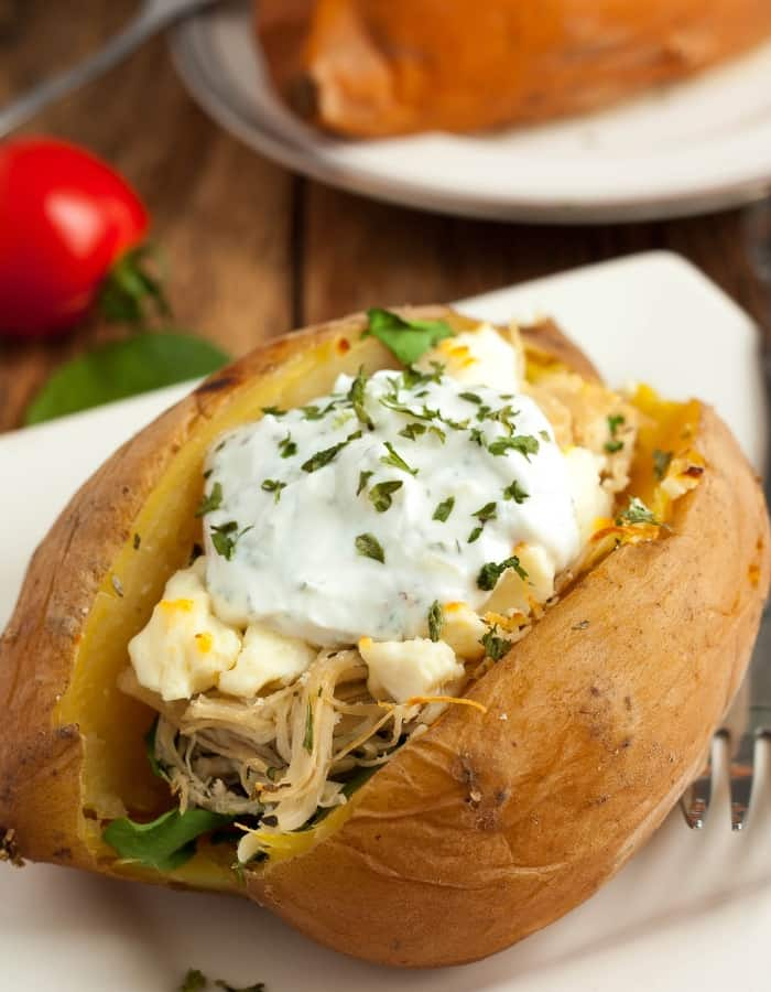 a sweet potato stuffed with spinach, shredded chicken, and greek yogurt sauce