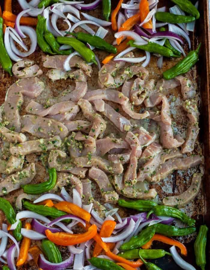 pork, peppers, and onions on a sheet pan for making pork fajitas
