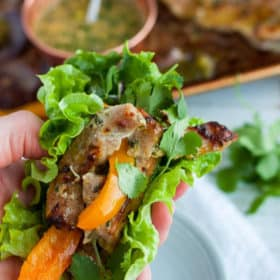 A hand holding a lettuce wrapped pork fajita with peppers and onions