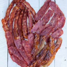A heart made out of bacon on a white board