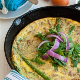 a paleo frittata in a cast iron skillet with greens and onion