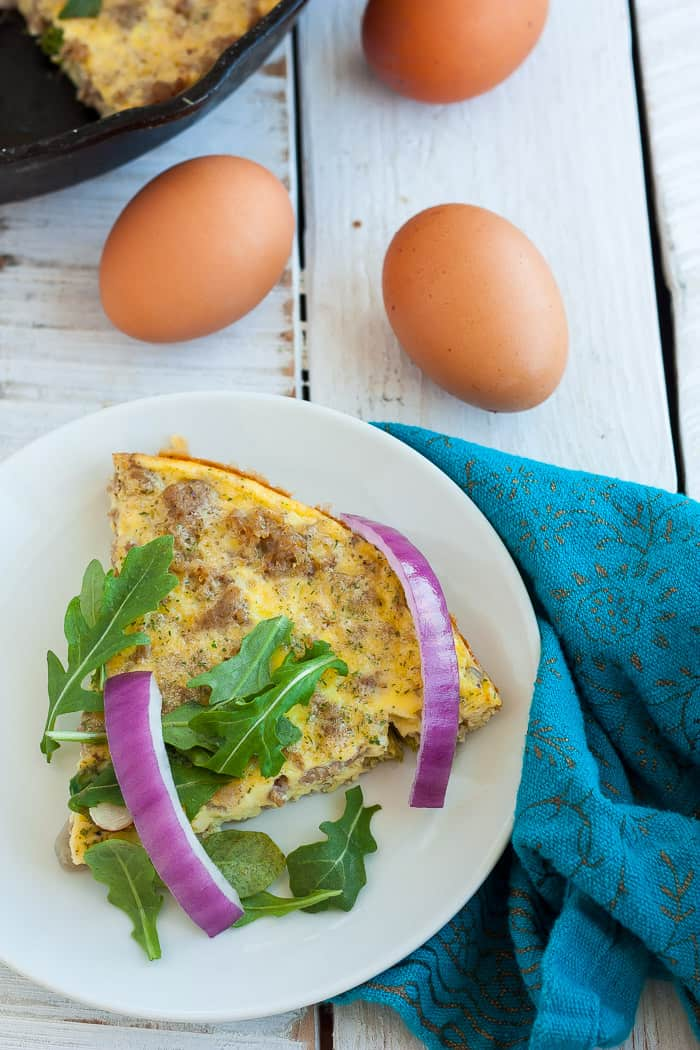 a slice of paleo frittata on a plate with eggs in the background