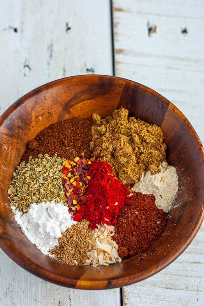 Various seasonings for making whole30 taco seasoning in a wooden bowl