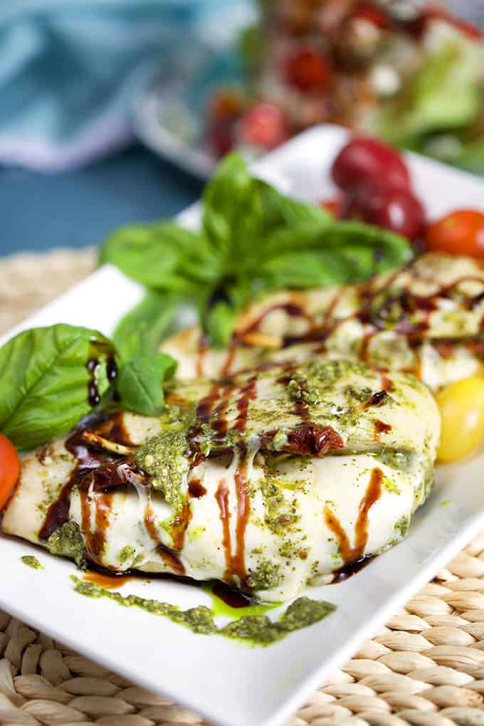 caprese stuffed chicken breast with balsamic and basil on a white plate