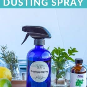 a blue bottle of homemade dusting spray with essential oils and a lemon and lime