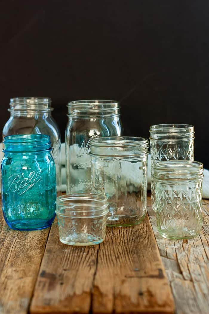 canning jars of different sizes on a wooden board