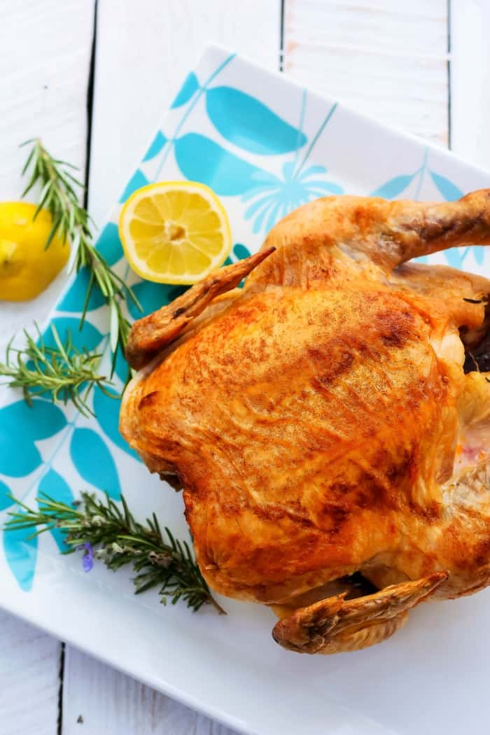 a paleo roasted whole chicken on a plate with rosemary and lemons