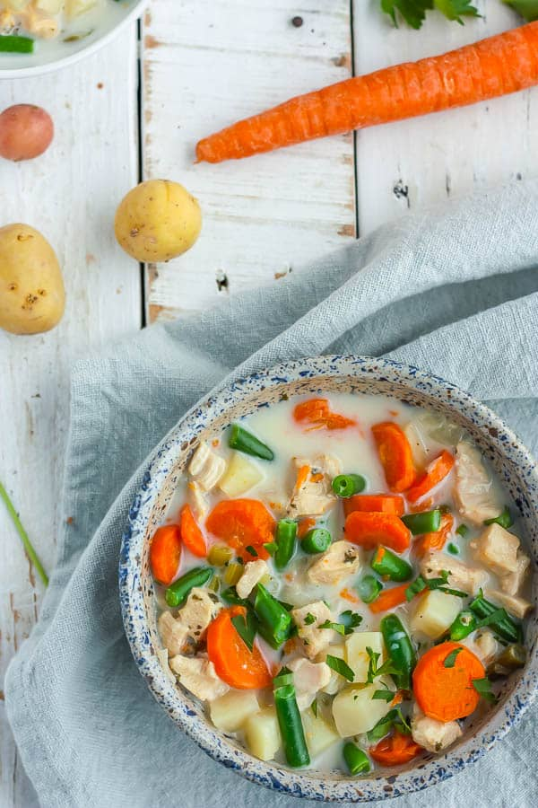 a bowl of paleo chicken pot pie soup with potatoe and carrots on a white board
