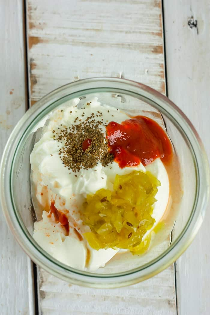 a bowl of greek yogurt and other ingredients for making sweet potato fries sauce