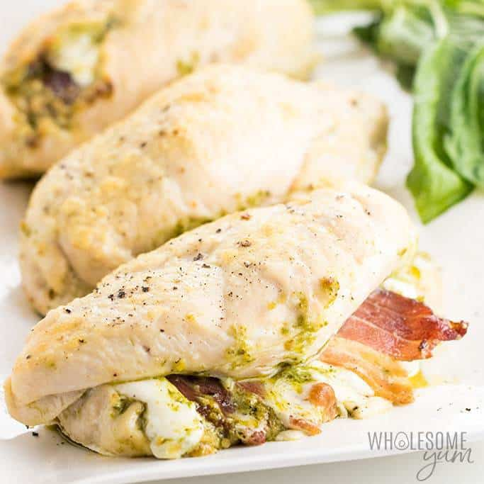 stuffed chicken breasts with bacon on a white plate with basil