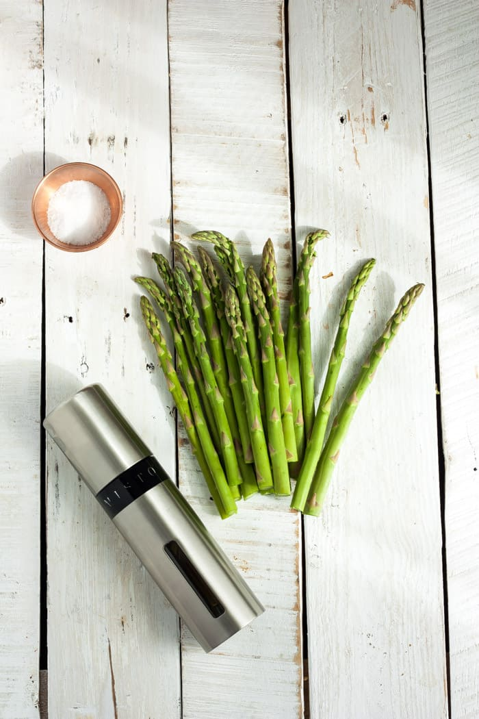 asparagus, an misto with olive oil and a bowl of salt on a white board