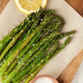 air fried asparagus with lemon and salt on a wooden board