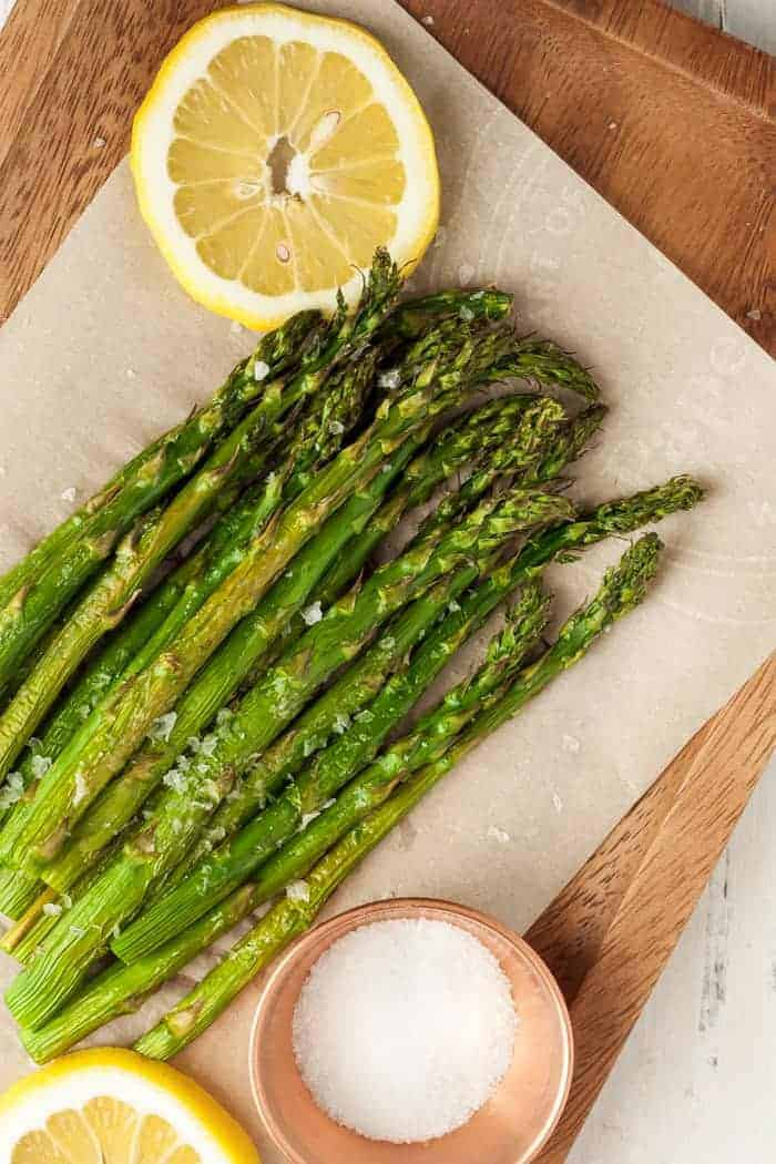 air fried asparagus on a wooden board with lemon slices and a bowl of salt