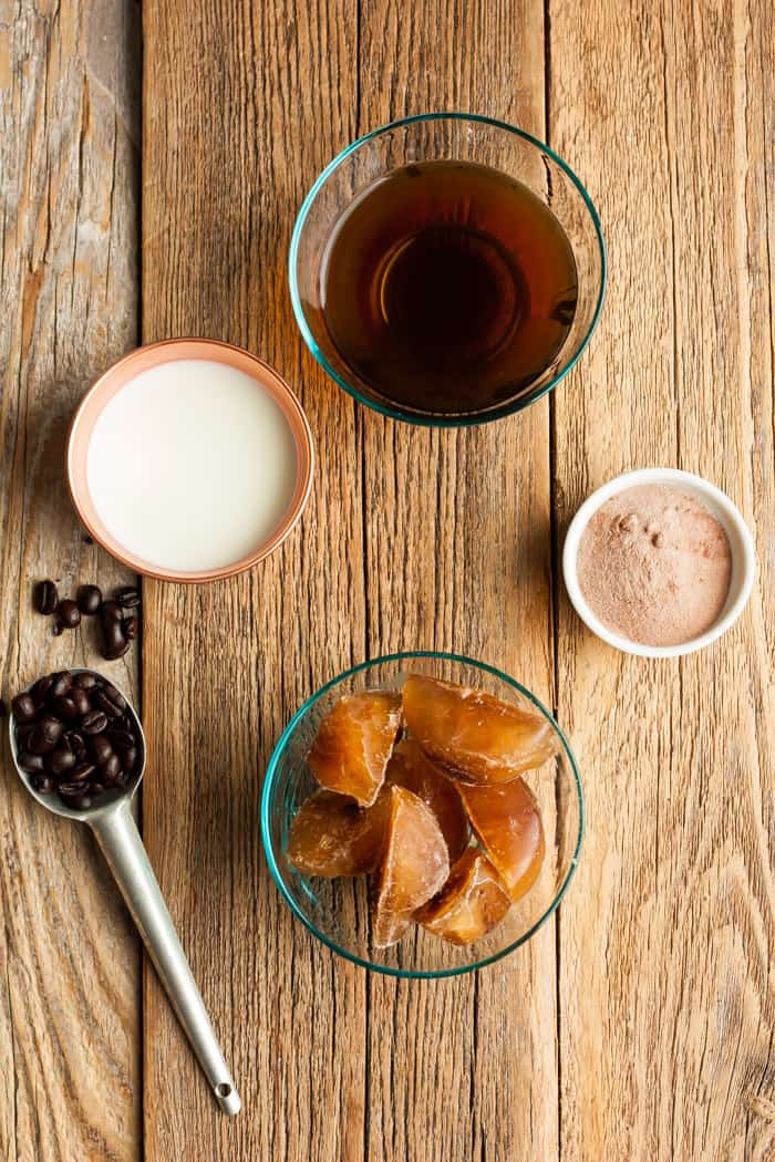 Bowls with coffee, milk, coffee ice cubes, and collagen powder on a wooden board