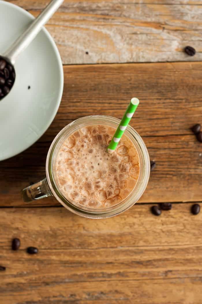 an overhead photo of frozen coffee in a canning jar with a straw