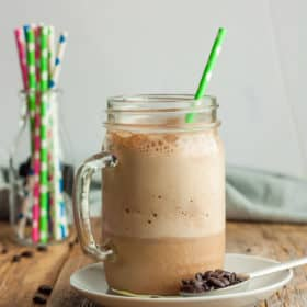 a canning jar glass of blended iced coffee with a green straw on a plate with a spoon and coffee beans.