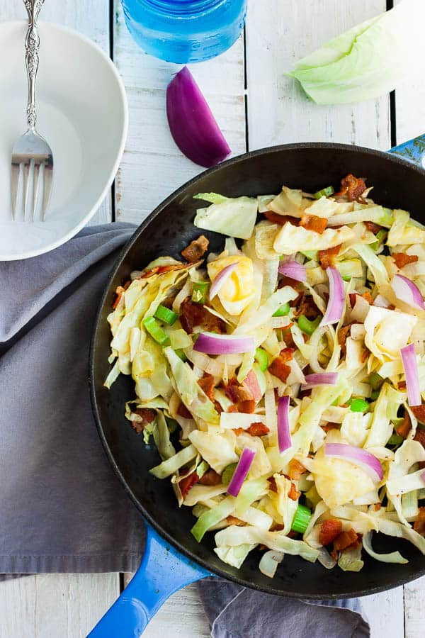 a skillet of fried cabbage and bacon with onion