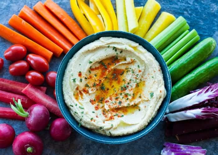 a bowl of hummus surrounded by a rainbow array of veggies