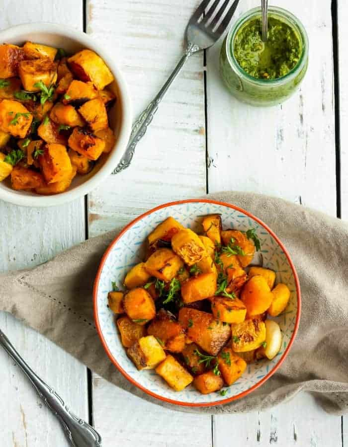 two plates of crispy butternut squash with a dish of chimichurri