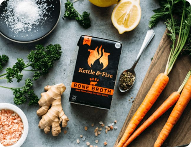 a container of kettle and fire bone broth with veggies on a gray board