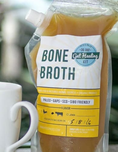 a container of pete's paleo bone broth with a mug