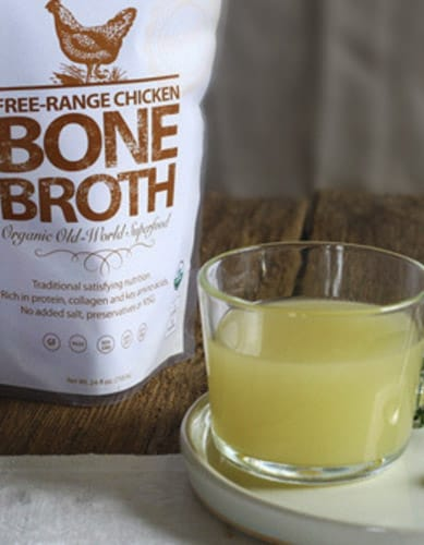 a glass and container of Vital Choice chicken bone broth