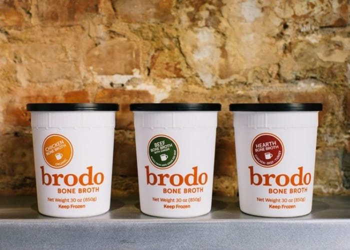 three containers of brodo bone broth against a brick wall
