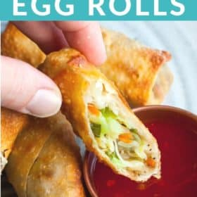 A hand dipping air fryer egg rolls into a bowl of dipping sauce