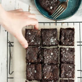 a hand reaching for a brownie on a baking rack