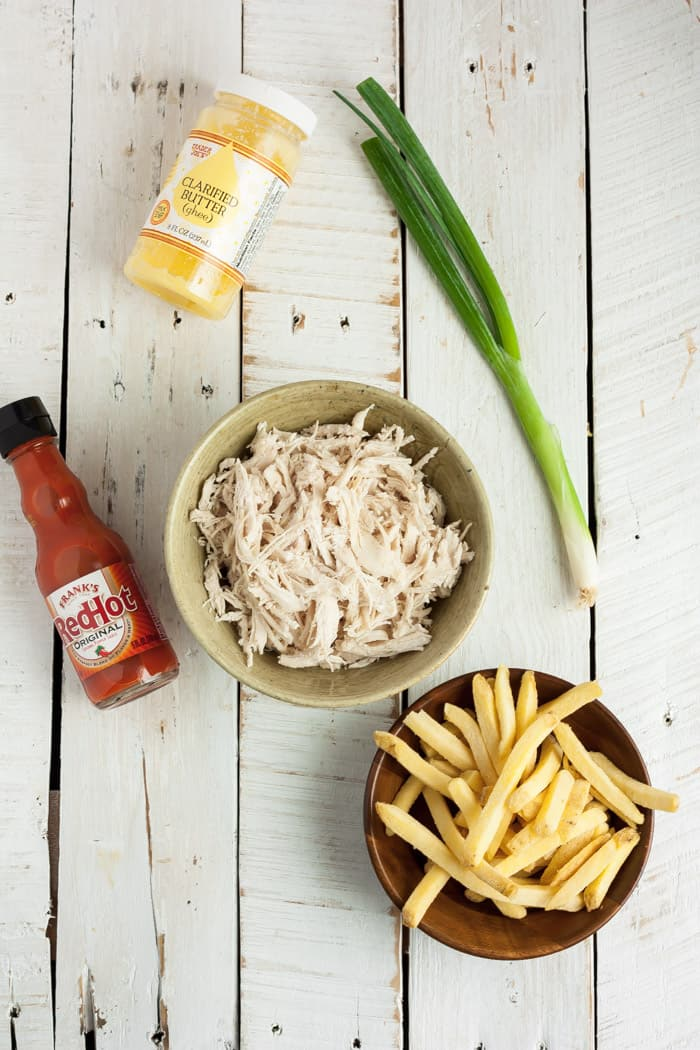 A bowl of shredded chicken, fries, and other ingredients for making buffalo chicken fries