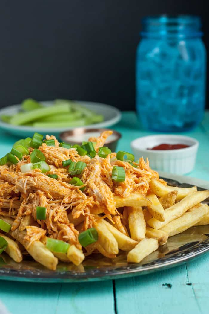 A plate of buffalo chicken fries topped with green onion