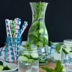 two glasses and a pitcher with cucumber mint water and a jar of paper straws