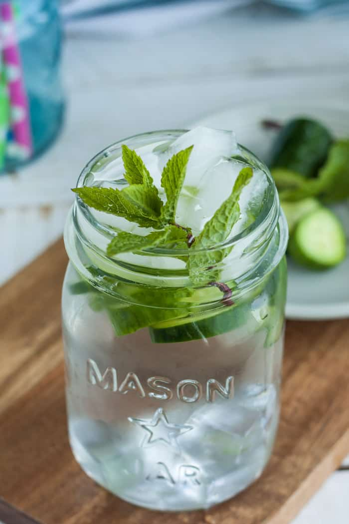 a mason jar with cucumber mint water on a wooden cutting board