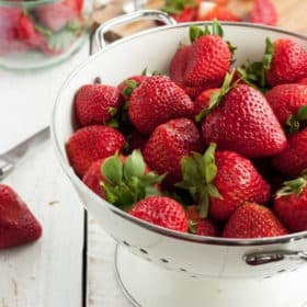 A strainer full of fresh strawberries and a cutting board