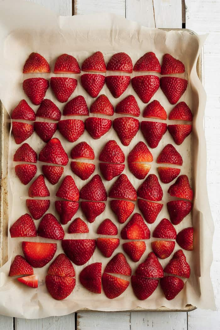 A baking tray with strawberries on parchment for freezing strawberries