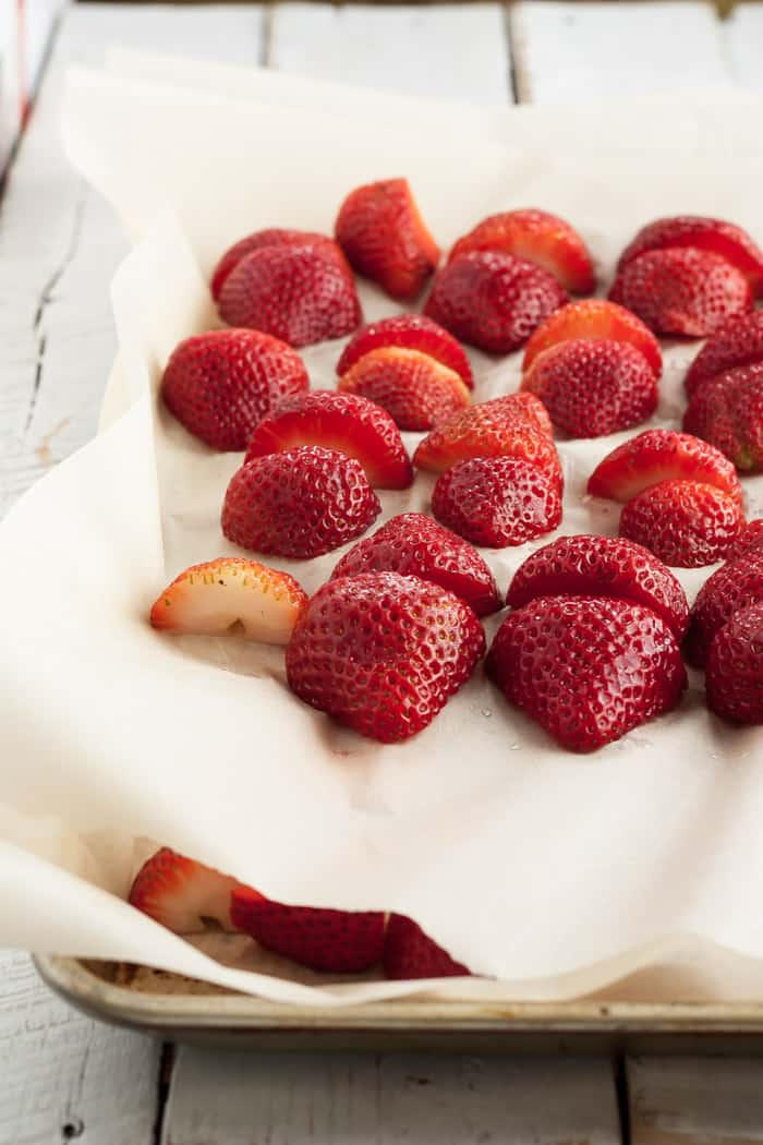 A baking sheet with two layers of parchment and strawberries for freezing