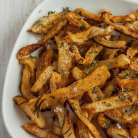 a plate of turnip fries with herbs