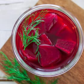 a glass jar of refrigerator pickled beets topped with fresh dill
