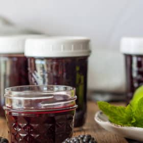 four jars of blackberry freezer jam with mint and blackberries
