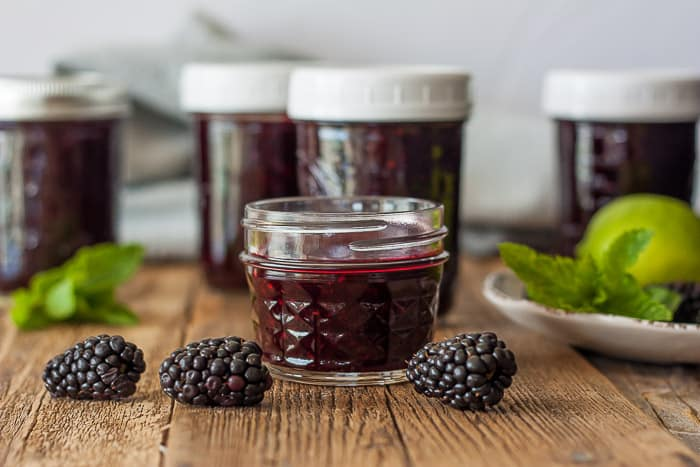 jars of blackberry freezer jam with fresh blackberries on a wooden board