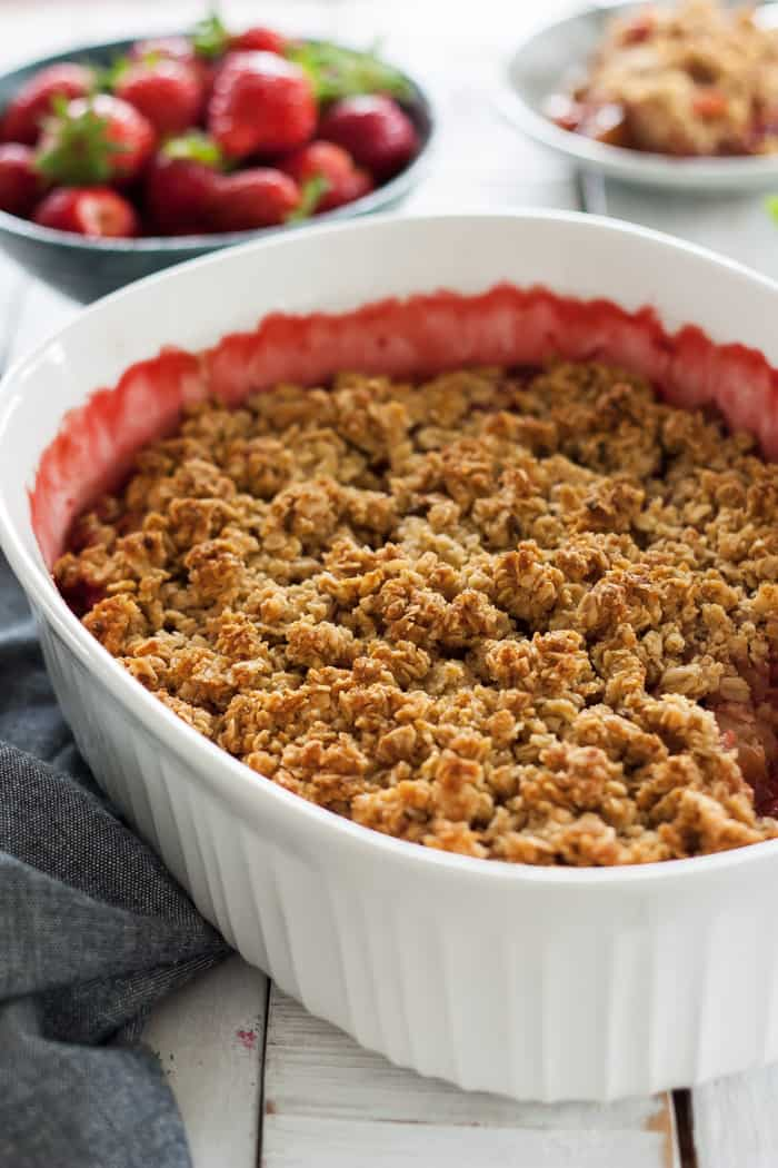 strawberry rhubarb crisp in a white baking dish with a bowl of strawberries