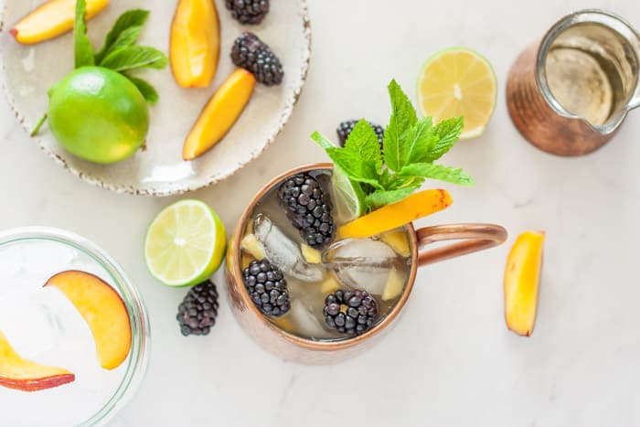 an overhead shot of a peach moscow mule with garnishes on a plate and a bowl of ice