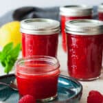 4 jars of raspberry freezer jam on a white board with mint and a lemon