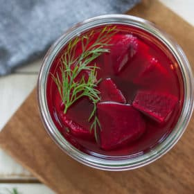 a jar of pickled beets on a wooden cutting board