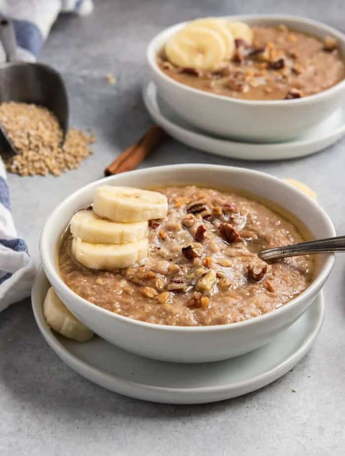two bowls of banana bread steel cut oats with sliced bananas