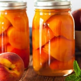 Jars of canned peaches on a wooden board