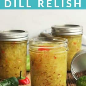 3 small jars of dill relish with cucumbers and spices on a wooden board