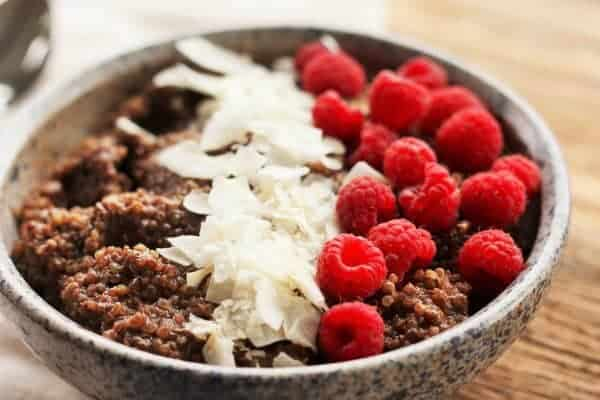 a chocolate quinoa breakfast bowl with coconut and raspberries